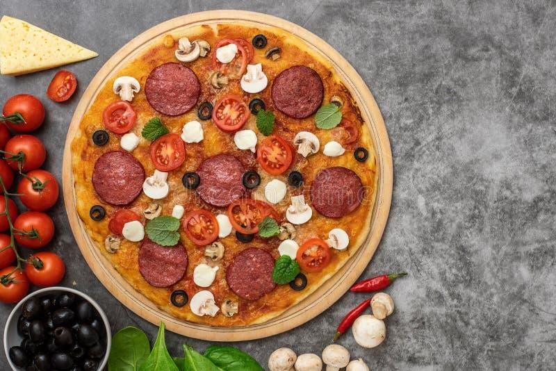 Pizza con queso, la mozzarella, las setas y el salami en fondo gris Visión superior fotos de archivo