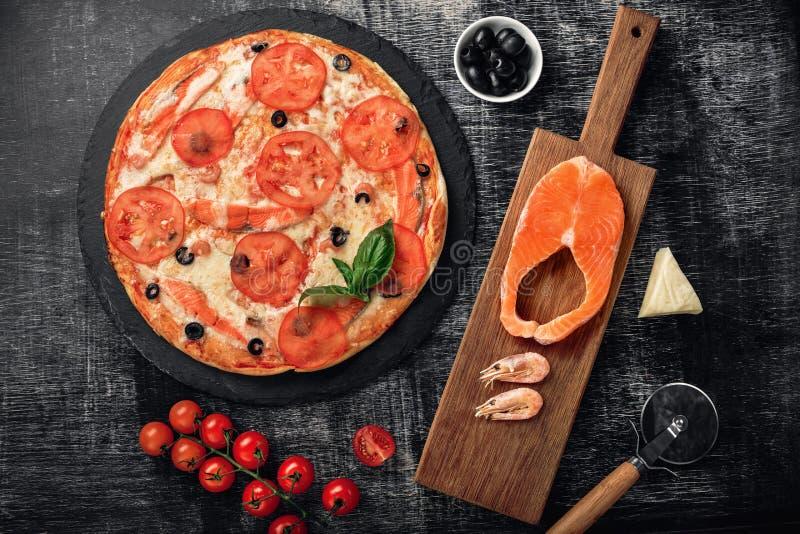 Pizza con queso, la trucha, los tomates, las aceitunas y los camarones en el tablero de tiza imagenes de archivo