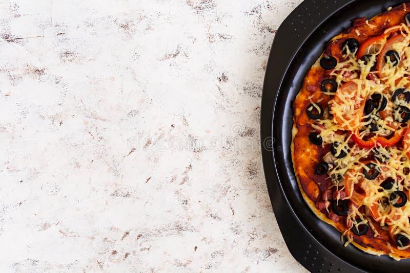 Pizza con salame, peperoni, i funghi e le olive su fondo bianco Vista superiore immagine stock