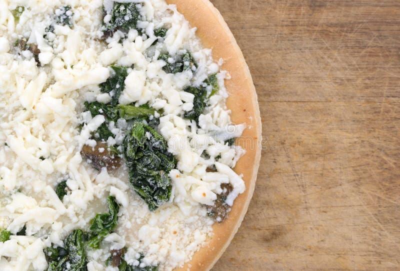 Pizza congelada cogumelo dos espinafres em uma placa de corte fotografia de stock