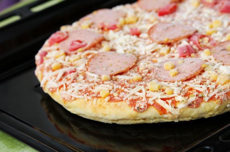 Pizza congelada com salame, queijo, milho e pimenta foto de stock