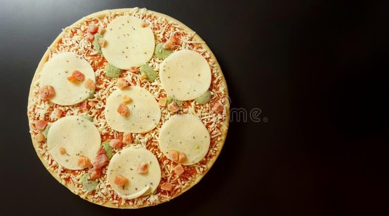 Pizza congelada redonda Tomates, mozzarella, pesto, albahaca Fondo de antracita imagen de archivo