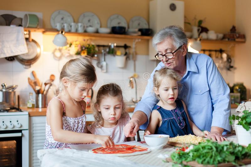 Pizza cooking class for kids, children chef. Cute girls are preparing italian food. Family dinner in cozy home kitchen. royalty free stock images