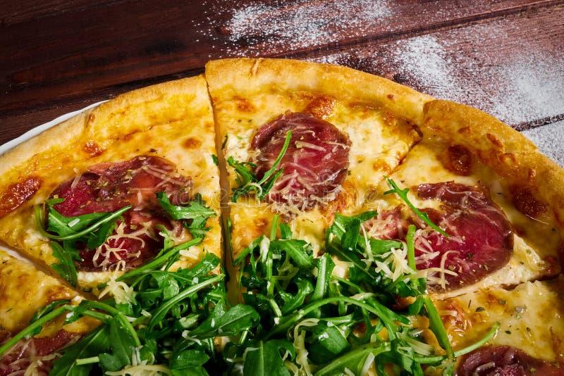 Pizza cortada con carne de vaca y cierre-u de los verdes imágenes de archivo libres de regalías