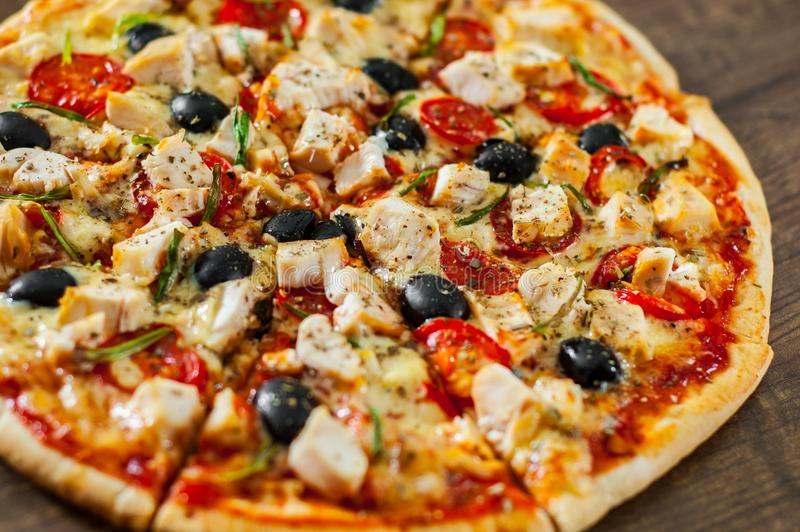 Pizza cortada con la carne del pollo, queso de la mozzarella, tomate, aceituna fotos de archivo libres de regalías
