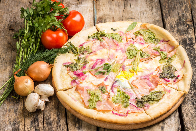 Pizza cortada con las verduras alrededor foto de archivo