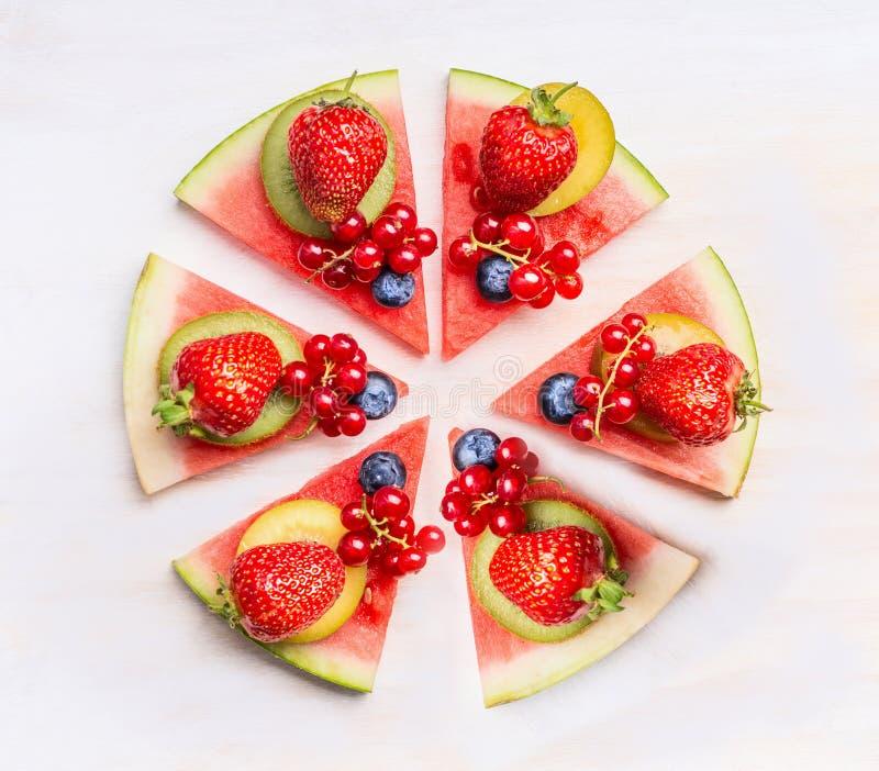 Pizza cortada de la sandía con las frutas y las bayas en el fondo de madera blanco, visión superior Alimento sano imagen de archivo