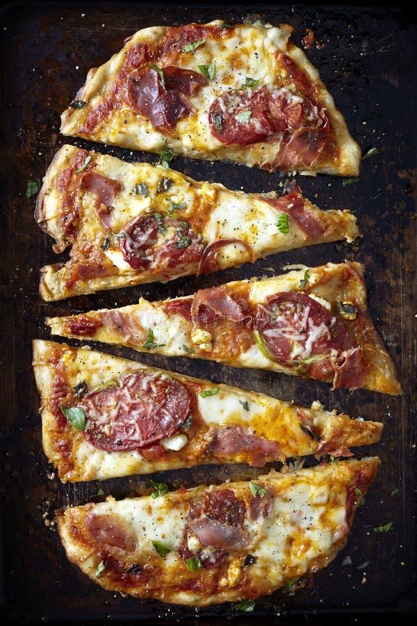 Pizza coupée en tranches d'artisan sur un fond foncé photographie stock libre de droits