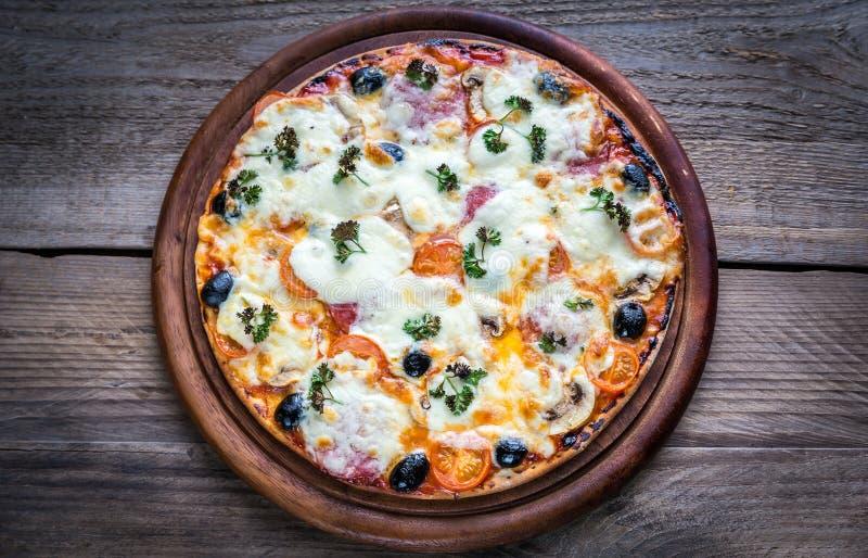 Pizza cozinhada na placa de madeira imagens de stock