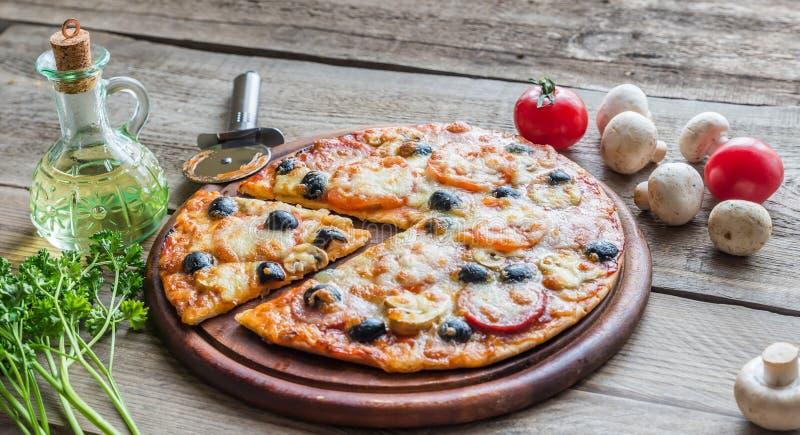 Pizza cozinhada na placa de madeira fotos de stock