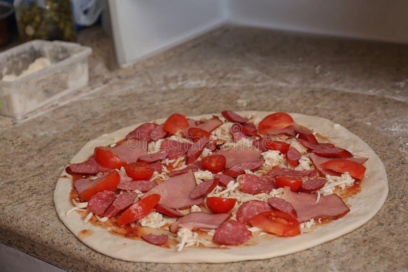 Pizza cru com coberturas diferentes Receita do forno fotografia de stock royalty free