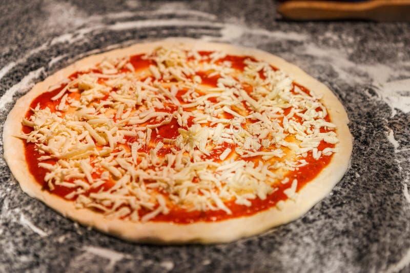 Pizza cruda con salsa al pomodoro e formaggio grattugiato immagini stock