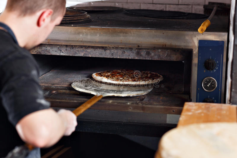 Pizza cruda pronta da cuocere nel forno Cucini in un grembiule blu nella cucina con una pala in sue mani fotografia stock libera da diritti
