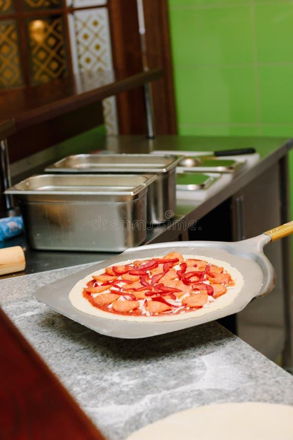 Pizza cruda sulla pala della pizza sulla cucina italiana del ristorante fotografia stock libera da diritti