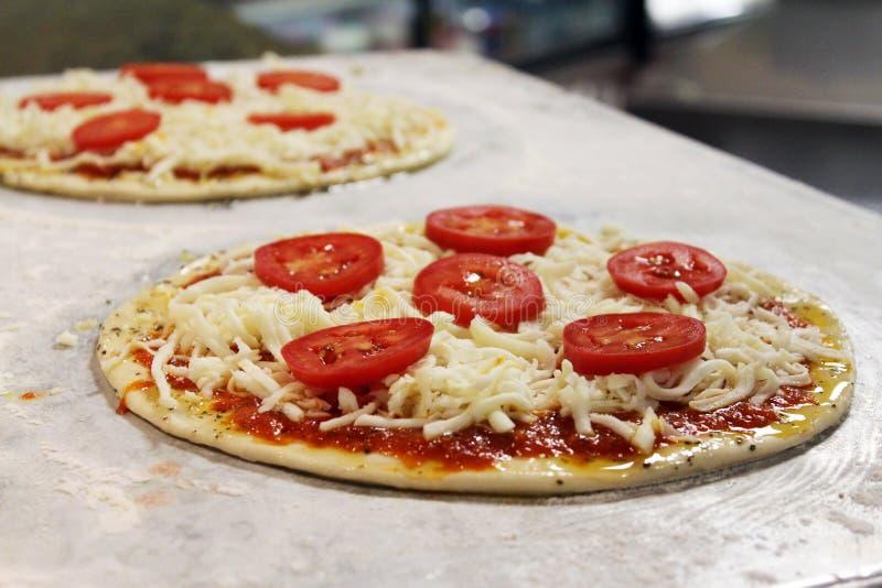 Pizza crue étant préparée sur une table d'acier inoxydable photo libre de droits