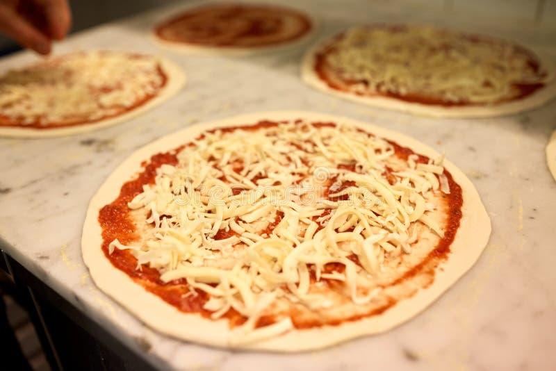Pizza crue avec du fromage râpé sur la table à la pizzeria image stock