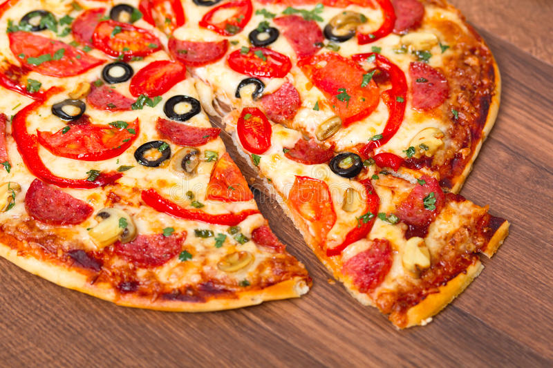 Pizza with the cut off slice. On wooden board stock photos