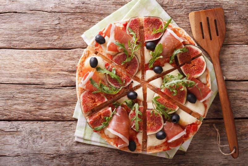 Pizza délicieuse avec le macro de figues, de jambon, d'arugula et de fromage horizo photo libre de droits
