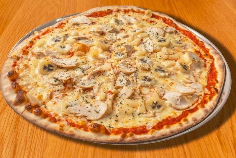 Pizza da galinha, da banana, do abacaxi e do creme em uma tabela de madeira fotografia de stock royalty free