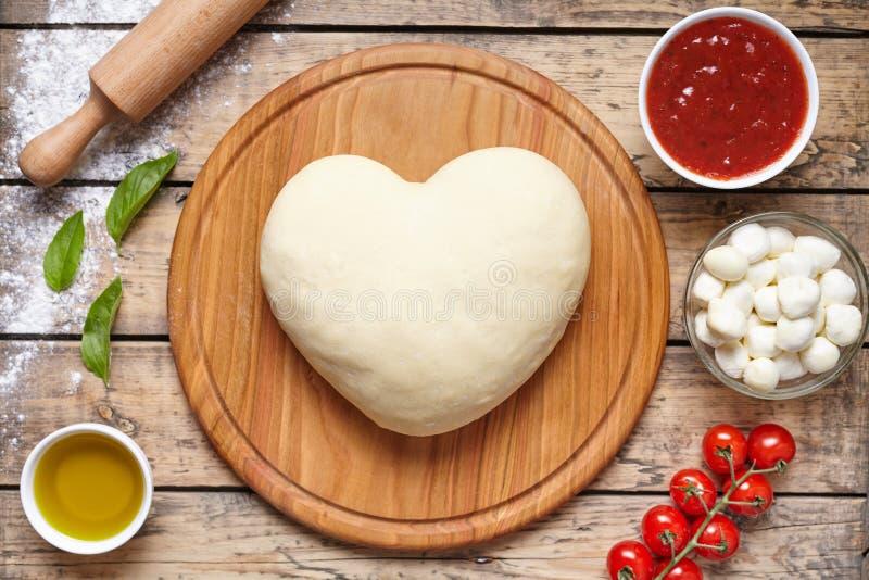 Pizza dada forma coração que cozinha ingredientes Massa, mussarela, tomates, manjericão, azeite, especiarias Trabalho com a massa imagens de stock royalty free