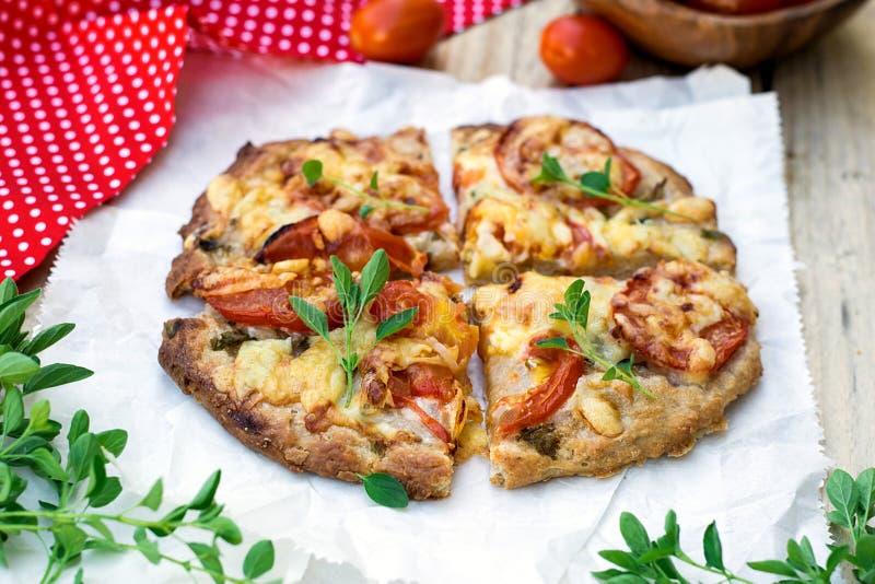 Pizza de blé entier avec les tomates, le fromage et les herbes images libres de droits