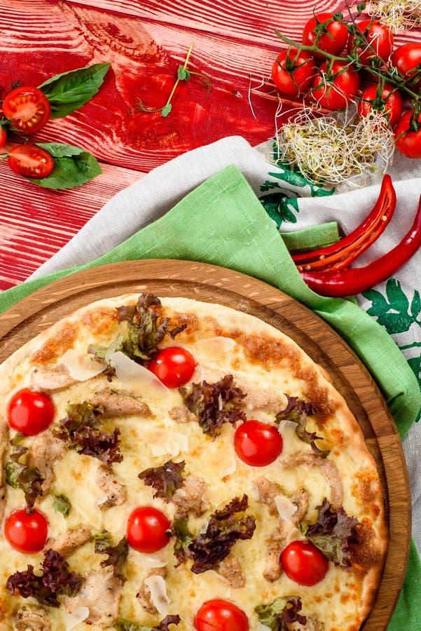Pizza de César avec du fromage, les tomates-cerises, le poulet et la laitue sur un conseil en bois rond sur un fond en bois rouge image libre de droits