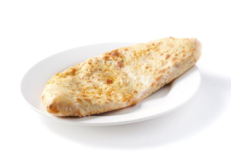 Pizza de Calzone em uma placa retangular em um fundo branco isolado fotografia de stock royalty free