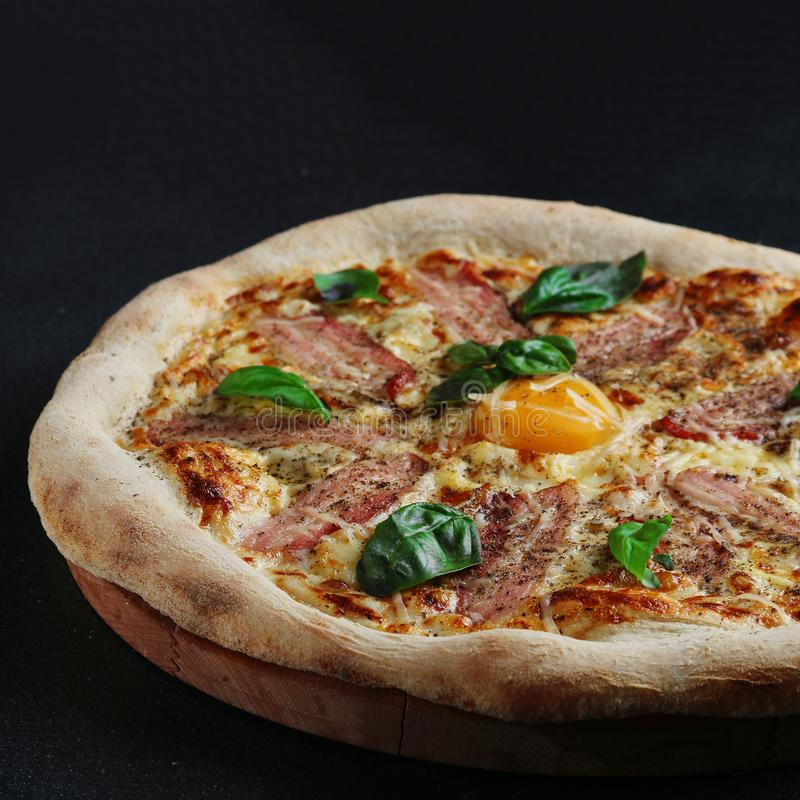 Pizza de Carbonara con el becon del huevo y hoja de la albahaca en fondo oscuro fotografía de archivo libre de regalías