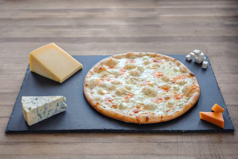 Pizza de fromage sur une ardoise parmi des morceaux de fromage photos stock