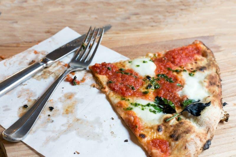 Pizza de las FO del pedazo de la visión superior con los tomates, la mozzarella, la albahaca y los cubiertos en la tabla de mader fotografía de archivo