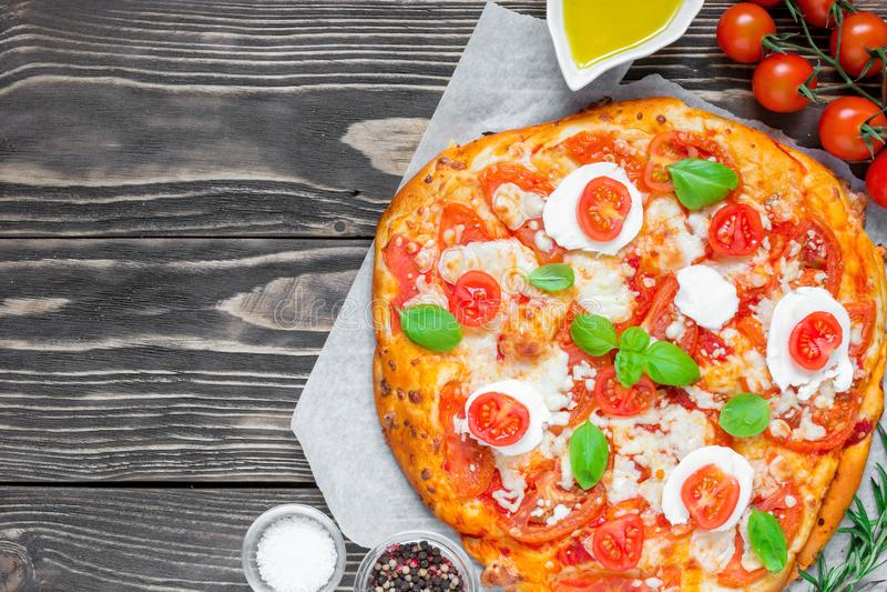 Pizza de Margherita Italian con queso derretido de la mozzarella, el tomate y la albahaca fresca foto de archivo libre de regalías