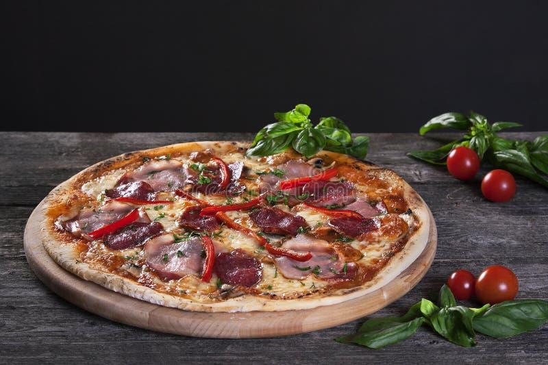 Pizza de pepperoni avec le salami, le lard, le poivron rouge et les oignons verts photos libres de droits