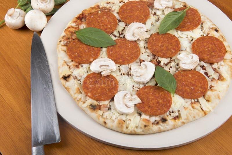 Pizza de pepperoni crue avec les champignons, le basilic, et un couteau images stock