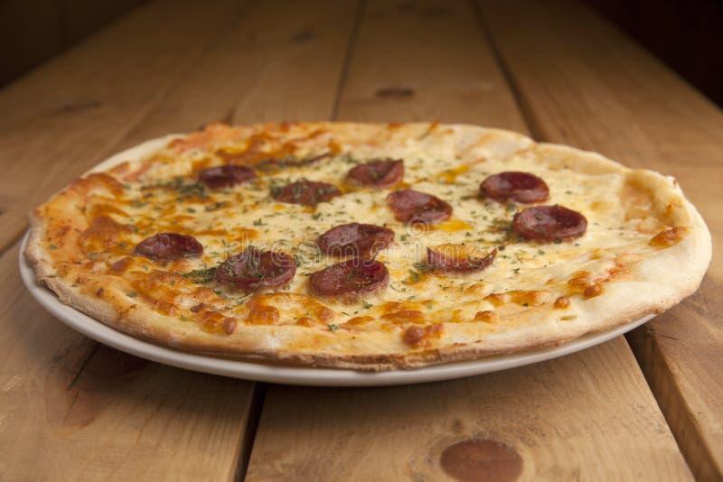Pizza de pepperoni délicieuse sur une table en bois image stock