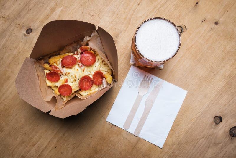 Pizza de pepperoni sur des fritures et une bière photos stock