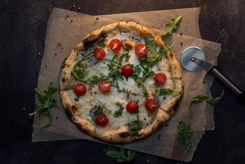 Pizza de queijo com papel e faca na opinião superior do fundo concreto escuro imagem de stock royalty free