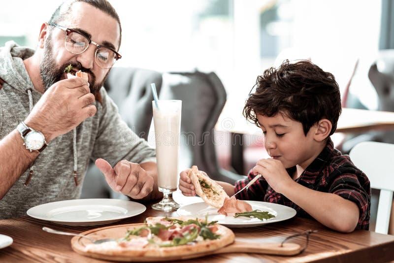 Pizza de queijo de irradiação engraçada comer feliz do sentimento do filho com pai imagens de stock royalty free