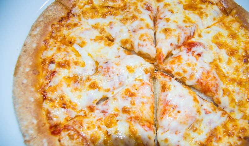 A pizza de queijo recentemente cozida, corte apetitoso em partes encontra-se em uma placa branca, vista superior fotos de stock