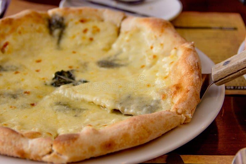 Pizza de queso deliciosa en la placa en un restaurante Caliente y preparado, con las hojas de la albahaca y el queso verde mohoso imágenes de archivo libres de regalías