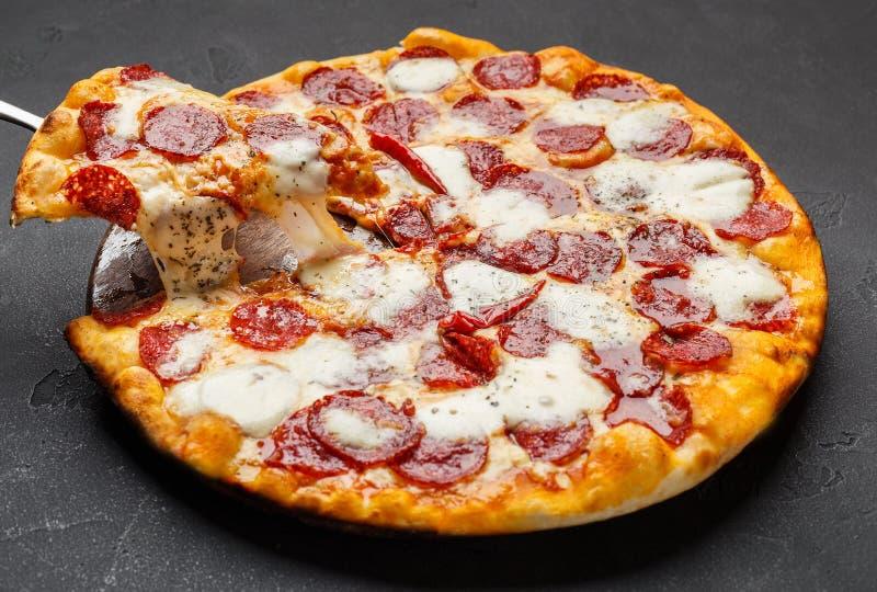 Pizza de salchichones caliente con queso de fusión en la tabla imágenes de archivo libres de regalías