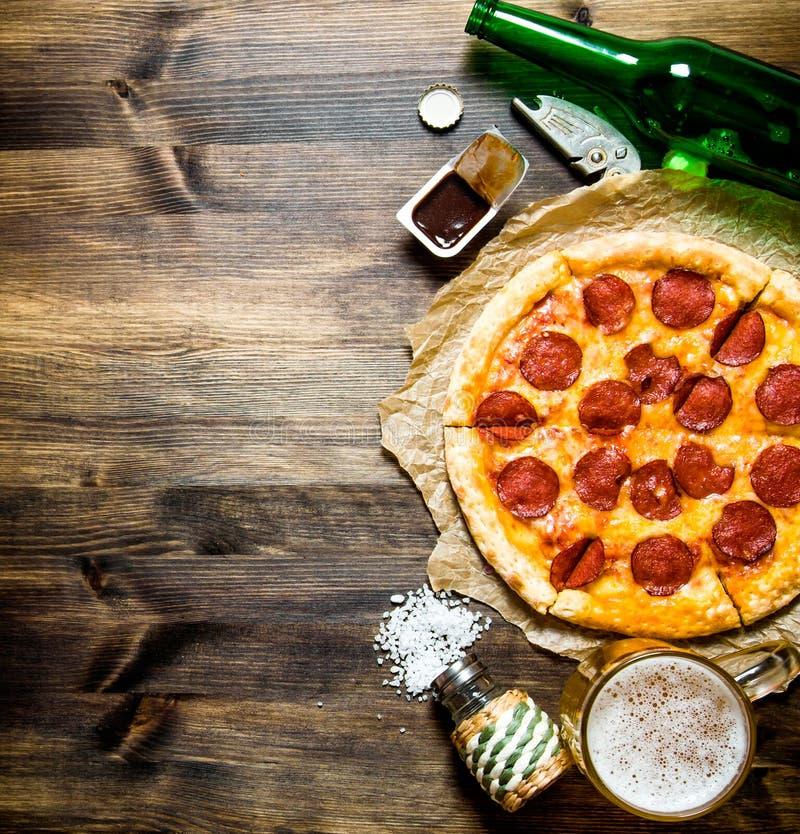 Pizza de salchichones con la cerveza en una tabla de madera fotos de archivo