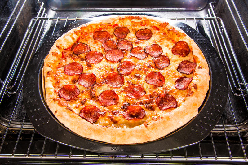 Pizza de salchichones en el horno fotografía de archivo