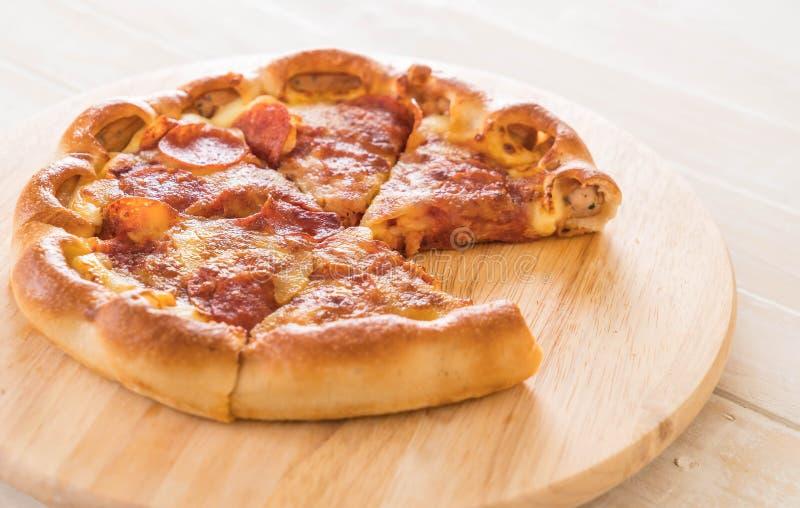 Pizza de salchichones hecha en casa en la placa de madera fotografía de archivo