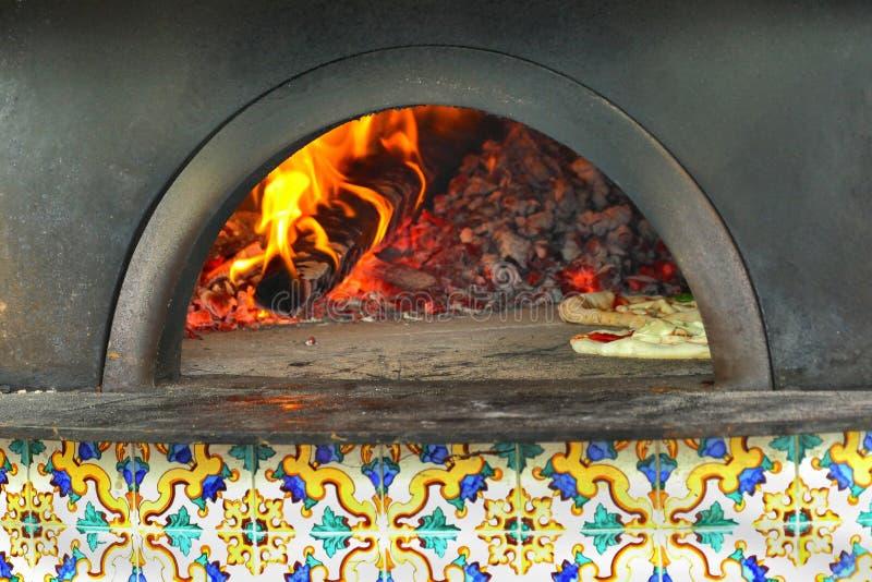 Pizza in de traditionele houten-brandt oven wordt gebakken die stock afbeelding