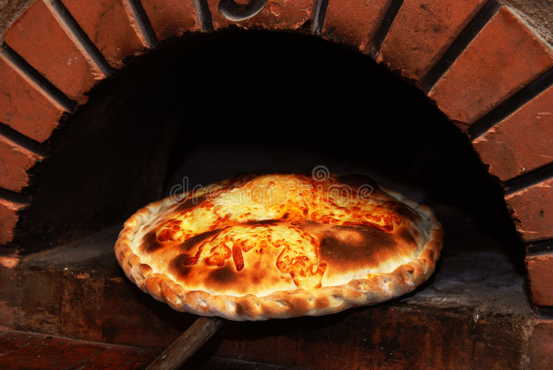 Pizza de un horno del ladrillo fotografía de archivo