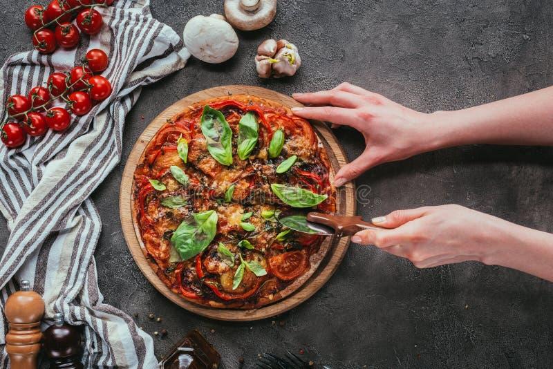 Pizza del corte de la mujer con el cuchillo imagenes de archivo