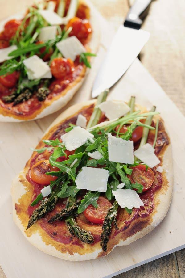 Comida: Pizza del tomate del espárrago, del cohete y de cereza con parmesano imagen de archivo libre de regalías