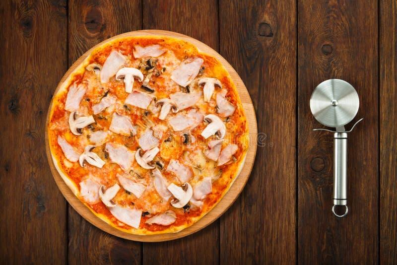 Pizza deliciosa com cogumelos e galinha fumado e cortador fotografia de stock royalty free