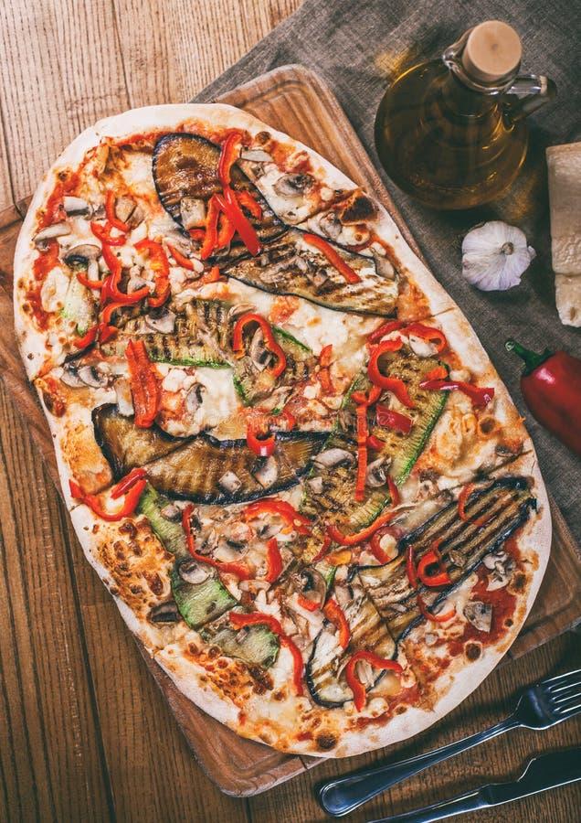 Pizza deliciosa con el pollo, el calabacín, la berenjena, la pimienta, el queso y las setas en la tabla rústica de madera foto de archivo libre de regalías