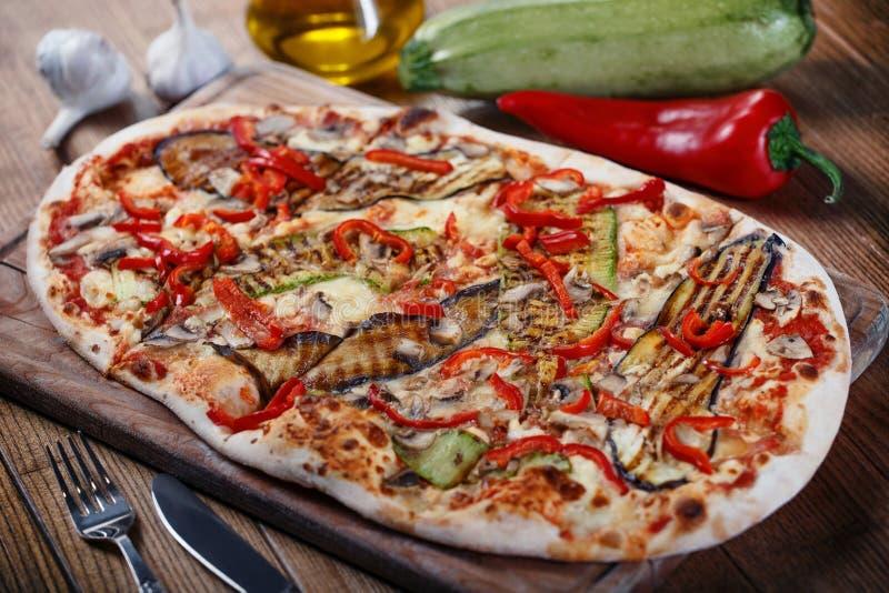Pizza deliciosa con el pollo, el calabacín, la berenjena, la pimienta, el queso y las setas en la tabla rústica de madera fotografía de archivo libre de regalías